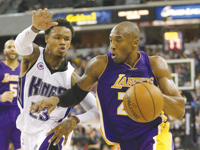 Los Angeles Lakers guard Kobe Bryant, right, drives to the basket against Sacramento Kings guard Ben McLemore on Sunday in Sacramento.