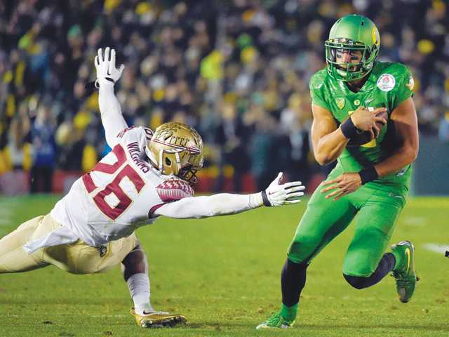 Oregon quarterback Marcus Mariota, right, scores past Florida State defensive back P.J. Williams during the Rose Bowl on Thursday in Pasadena.