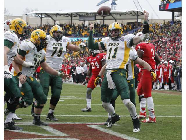 North Dakota State quarterback Carson Wentz (11) celebrates the go-ahead touchdown against the Illinois State with teammates in the second half of the FCS Championship game on Saturday in Frisco, Texas.