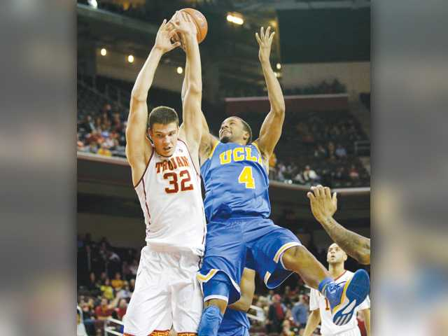 UCLA 's Norman Powell, right, is fouled by USC's Nikola Jovanovic during Wednesday's game in Los Angeles.