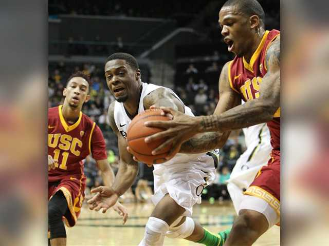 Southern California's Jordan McLaughlin, left, and Darion Clark, right, battle Oregon's Elgin Cook, center, for a loose ball during the first half of an NCAA college basketball game in Eugene, Ore. on Thursday.