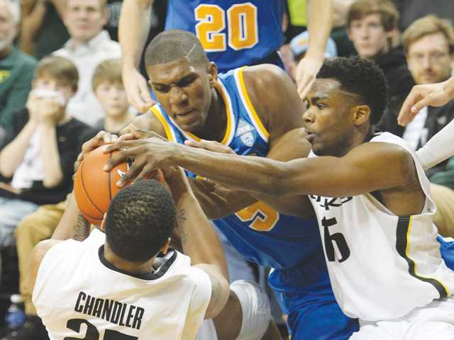 Oregon's Michael Chandler, left, UCLA's Kevon Looney, center, and Oregon's Jalil Abdul-Bassit, right, fight for a loose ball on Saturday in Eugene, Ore.