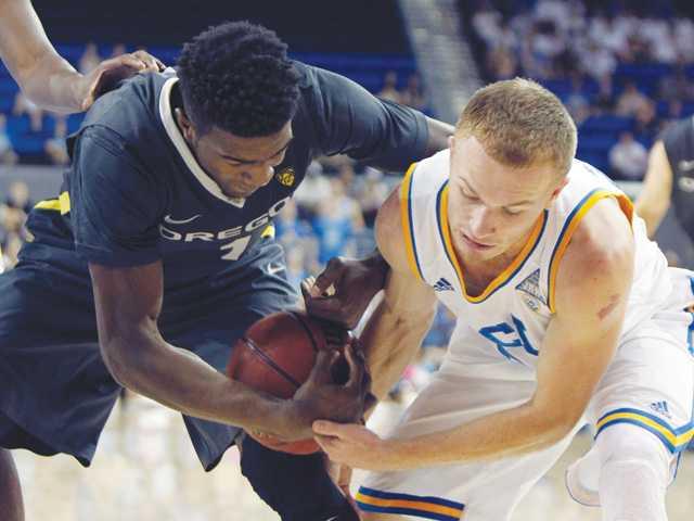 Oregon forward Jordan Bell, left, battles UCLA guard Bryce Alford on Saturday in Los Angeles.