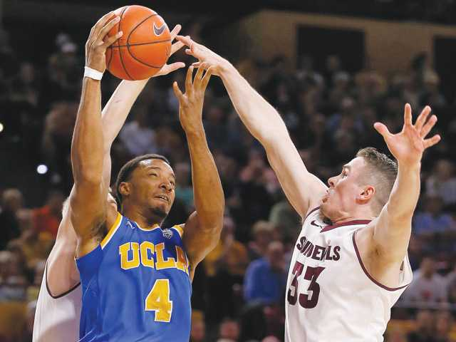UCLA's Norman Powell (4) shoots over Arizona State's Bo Barnes (33) on Wednesday in Tempe, Ariz.