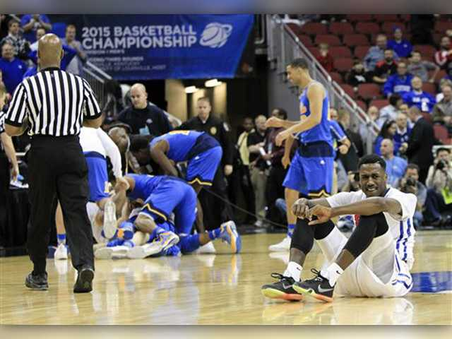 SMU guard Ryan Manuel, right, sits on the floor as UCLA celebrates after Bryce Alford made a 3-point basket in the closing seconds of the second half of an NCAA tournament game in Louisville, Ky., Thursday.AP Photo/David Stephenson