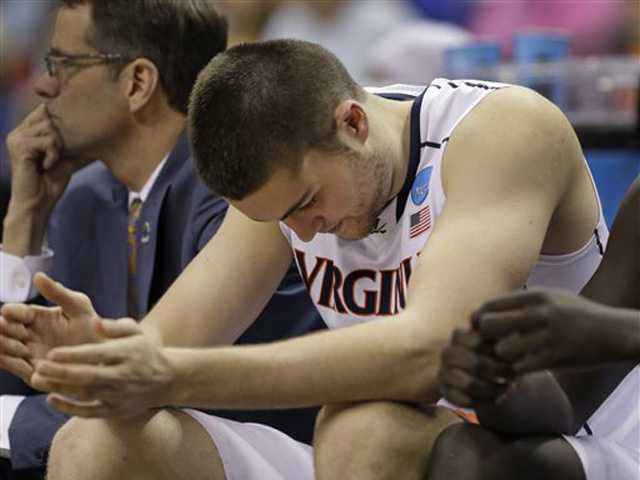 Virginia's Mike Tobey sits on the bench in the final moments of the second half of an NCAA tournament game against Michigan State in Charlotte, N.C., Sunday. AP Photo/Gerald Herbert