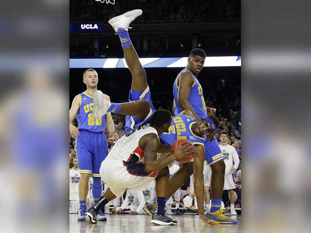 UCLA's Kevon Looney (5) falls over Gonzaga's Gary Bell Jr. during the second half of a regional semifinal game in the NCAA Tournament Friday in Houston. AP Photo/David J. Phillip