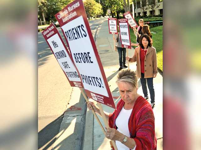Robbie Bailey pickets with other nurses and supporters near Henry Mayo Newhall Hospital on the corner of McBean Parkway and Orchard Village on Thursday. Signal photo by Katharine Lotze