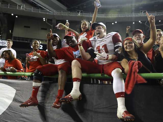 Western Kentucky defensive lineman Tanner Reeves (11) celebrates with the fans after Western Kentucky defeated South Florida in the Miami Beach Bowl game on Monday in Miami.