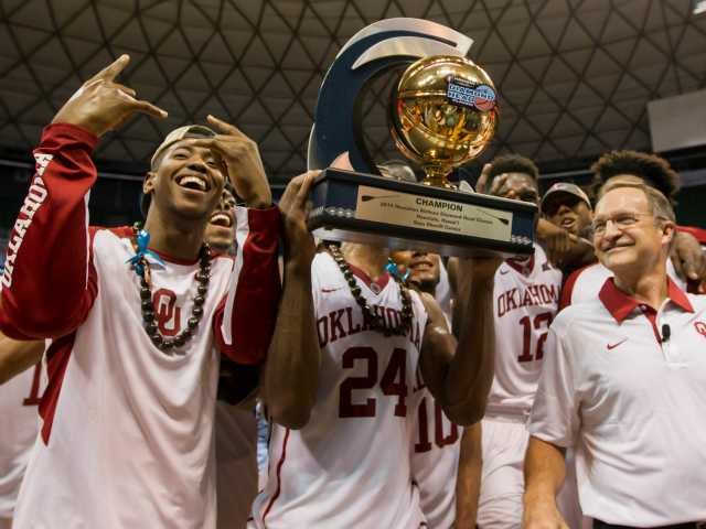 Oklahoma head coach Lon Kruger, right, smiles and looks on as his team poses for a picture with the Diamond Head Classic championship trophy after an NCAA college basketball game against Harvard on Friday.