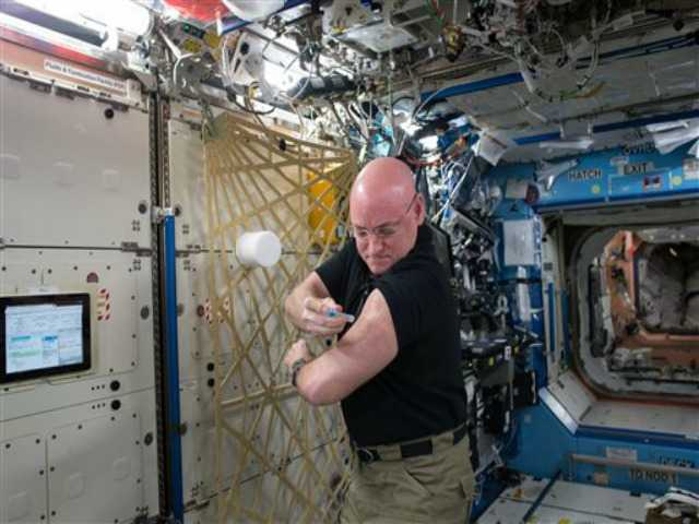 In this Sept. 24, 2015 photo made available by NASA, astronaut Scott Kelly gives himself a flu shot aboard the International Space Station for an ongoing study on the human immune system.