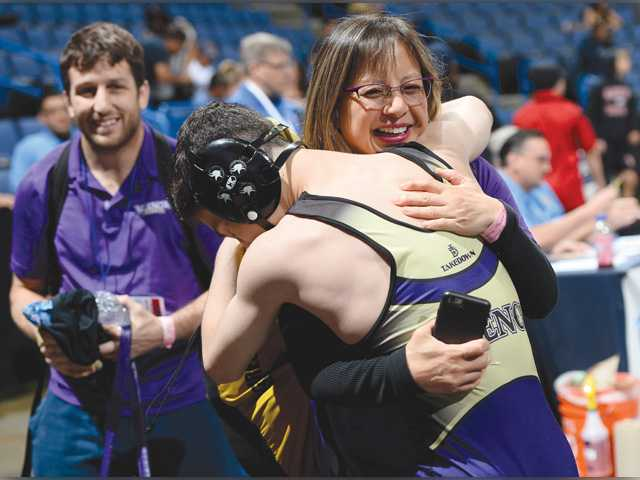 Valencia wrestler Chance Rich, front, gets a hug from assistant coach Felicia Oh, as head coach Brian Peterson looks on after Rich pinned Servite's Liam Cronin in Saturday's semifinal at the CIF-SS Masters Meet in Ontario. Photo by Jayne Kamin-Oncea/For The Signal