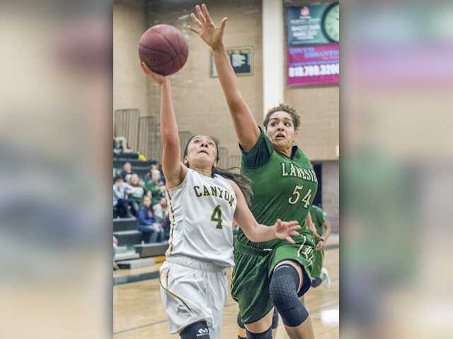 Canyon's Alaina Garcia (4) goes up for a shot as Lakeside center Emma Merriweather (54) defends at Golden Valley High on Saturday night. Photo by Tom Cruze/For The Signal