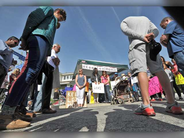 Demonstrators form a circle and pray on the corner of Ron Ridge Drive and Plamplico Drive in Saugus in the hope of preventing a foster daughter from being taken from her foster parents. County child welfare workers picked up the 6-year-old girl shortly after 2:30 p.m. Monday. Signal photo by Katharine Lotze.