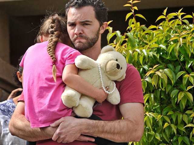 Foster father Rusty Page carries 6-year-old foster daughter Lexi to county car that will take her, along with county social workers, from the Saugus home where she has lived with the Page family four years. Signal photo by Katharine Lotze. Copyright 2016 Signal Multimedia