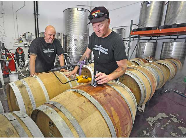Pulchella Winery has a tasting room in historic downtown Newhall (Santa Clarita) on Main Street. Above, co-owners and co-wine makers Steve Lemley, left, and Nate Hasper of Pulchella Winery transfer wine to barrels at their wine making facility. Photo by Dan Watson