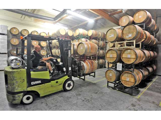 Co-owner and co-wine maker Steve Lemley moves barrels of wine in the Pulchella Winery wine cellar in Valencia. Photo by Dan Watson