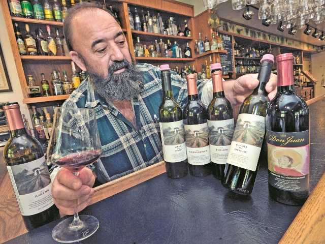 Juan Alonso in the Le Chene restaurant on Sierra Highway with bottles of wine he produced from the Alonso Family Vineyards. Photo by Dan Watson