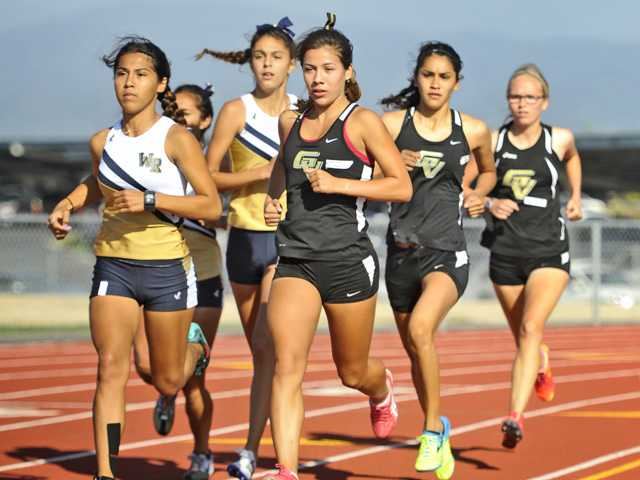 West Ranch's Siobhan Rubio, left, and Golden Valley's Bianca Tonoco, right, lead the pack in the varsity girls 1600 meter run during a dual meet at Golden Valley on Wednesday.Signal photo by Katharine Lotze.