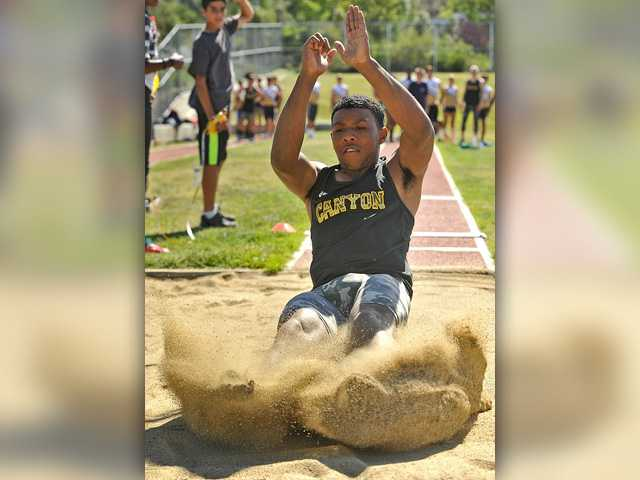 Canyon's Brandon Wilson lands a successful long jump during a dual meet at West Ranch on Thursday. Signal photo by Katharine Lotze.