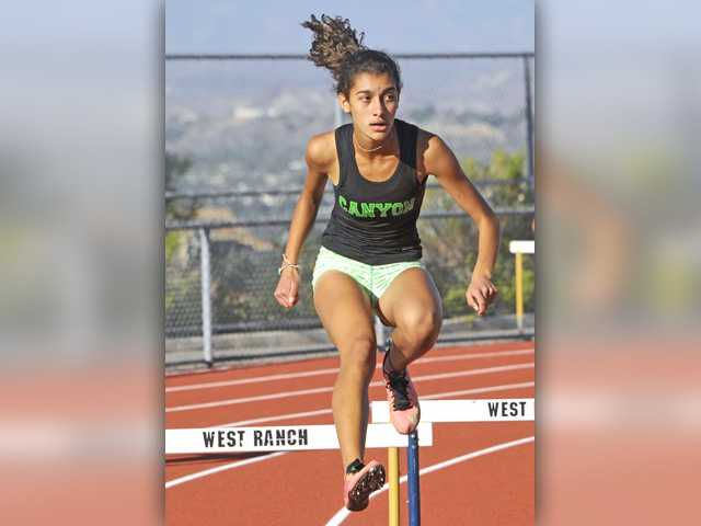 Canyon's Seanna Nalbandyan looks ahead as she clears a hurdle in the varsity girls 300 meter low hurdles during a dual meet at West Ranch on Thursday.Signal photo by Katharine Lotze.