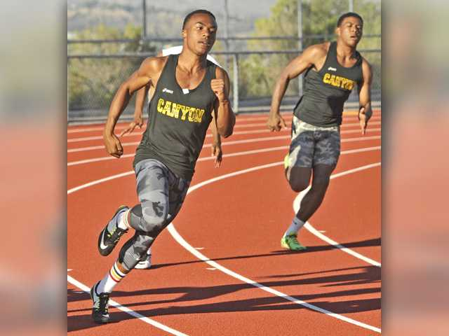 Canyon's Steven Arrington, left, and Brandon Wilson run the boys 100-meter dash during a dual meet at West Ranch on Thursday.Signal photo by Katharine Lotze.