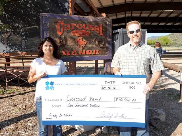 Denise Redmond, Executive Director of Carousel Ranch, receives check from Rawleigh Smith, president of Choices in Learning National Foundation. Courtesy photo