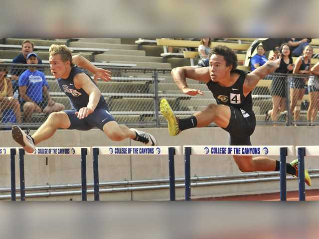 Saugus' Houston Heinemann and Golden Valley's Nathan Ray go head-to-head in the boys varsity 110-meter hurdles at the Foothill League track and field championships preliminaries at College of the Canyons on Tuesday. Signal photo by Katharine Lotze.