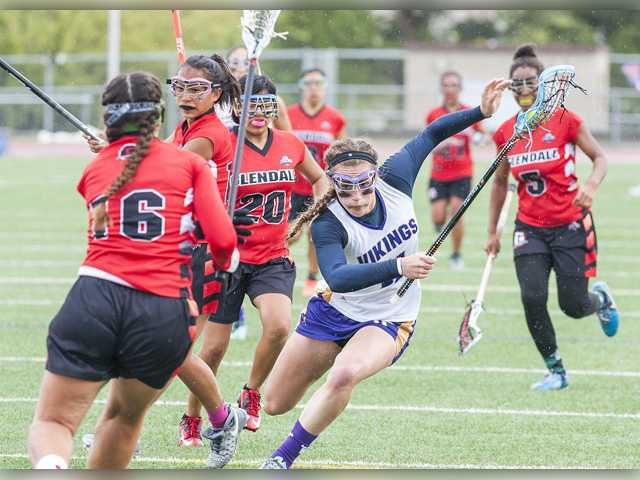 Valencia's Kayla Konrad, center, carries the ball to the net while defended by a host of Glendale defenders in the U.S. Lacrosse Southern Section Los Angeles Division 2 semifinals at Valencia on Friday. Photo by Tom Cruze for The Signal.