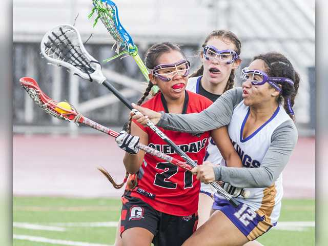Glendale High's Angel Ancheta (21) is defended by Valencia's Kiki Shakir (12) and Valencia's Jenny Elliot in the first half of their U.S. Lacrosse Southern Section Los Angeles Division 2 semifinal at Valencia on Friday. Photo by Tom Cruze for The Signal.