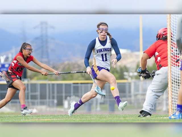 Valencia's Kayla Konrad (11) rushes the net as Glendale's Xcaret Salvador (left) defends and goalie Jenina Villabroza waits for the shot in the second half of their U.S. Lacrosse Southern Section Los Angeles Division 2 semifinal at Valencia on Friday. Photo by Tom Cruze for The Signal.