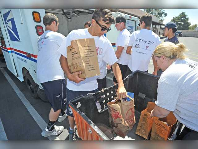 Volunteers from the West Ranch High School Action Team unload bags of donated food from postal trucks that were picked up by letter carriers making their postal deliveries as part of the Stamp Out Hunger Food Drive and brought to the U.S. Post Office, Valencia Branch to benefit the Santa Clarita Valley Food Bank on Saturday. Signal photo by Dan Watson.