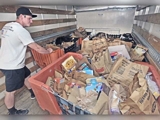 West Ranch High School Action Team volunteer, Doug Gragg rolls a cart full of bags of donated food into a truck destined for the Santa Clarita Valley Food Pantry as part of the Stamp Out Hunger Food Drive at the U.S. Post Office, Valencia Branch on Saturday. Signal photo by Dan Watson.