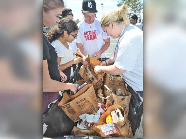 West Ranch High School Action Team volunteers fill a cart with of bags of donated food destined for the Santa Clarita Valley Food Pantry which were collected by U.S. Postal letter carries as part of the Stamp Out Hunger Food Drive at the U.S. Post Office, Valencia Branch on Saturday. Signal photo by Dan Watson.
