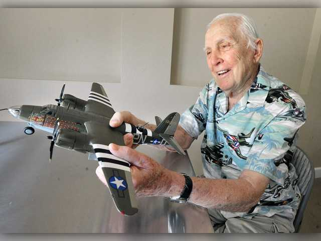 "U.S. Army Air Force veteran Lloyd ""Lou"" Lubensky, 93, holds a model of a Martin B-26 bomber painted with D-Day invasion markings as he remembers piloting two missions over the beaches of Normandy on D-Day, June 6, 1944. Signal photo by Dan Watson."