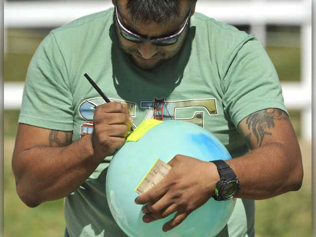 "Emmanuel Perdomo writes his ""burdens"" on a sticky note on an inflatable ball during a mock therapy session at Blue Star Ranch on March 30. Signal photo by Katharine Lotze."