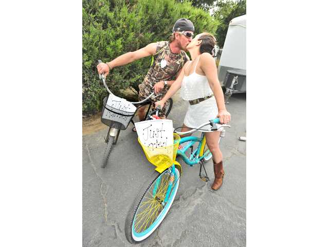 "Groom Erik Denton, left, and bride Michelle Ondrias sit on their bikes decorated with ""Just Married"" signs and trailing beer cans as they kiss after their wedding ceremony at the Castaic RV Park in Castaic on Saturday. Signal photo by Dan Watson."