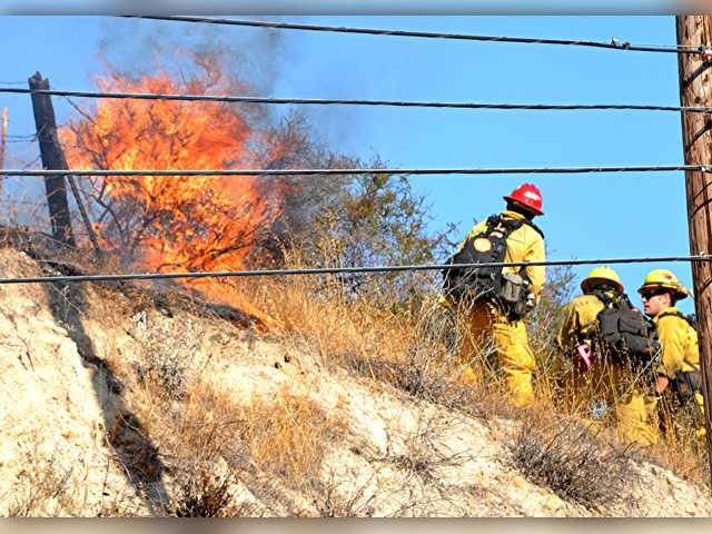 A firefighter battles flames off of Sierra Highway after a car crash reportedly sparked a fire. Photo for The Signal by Rick McClure.