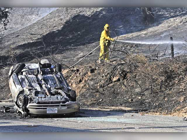 A firefighter mops up hot spots following a brush fire between Sierra Highway and southbound Highway 14 on Wednesday in Newhall. The fire was reportedly sparked when a vehicle flew from Highway 14 on fire.Signal photo by Katharine Lotze.