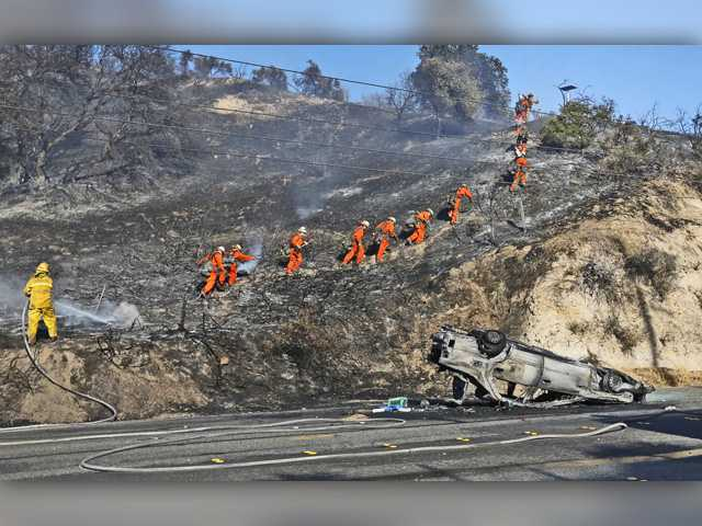 A camp crew climbs a hill off of Sierra Highway as a firefighter mops up hot spots where a car flew from Highway 14 on fire, and sparked a small brush fire in Newhall on Wednesday.Signal photo by Katharine Lotze.