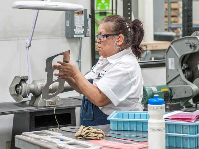 An employee at Lamsco West Inc. in Santa Clarita making laminated shims for aircraft. The firm is a supplier to Boeing. Photo by Tom Cruze/SCVBJ