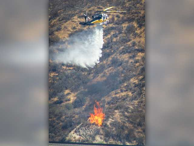 Helicopters drop water on the Sand Fire as fire crews work to contain it in Sand Canyon, California on Friday July 22, 2016. Signal photo by Jordan Glenn.