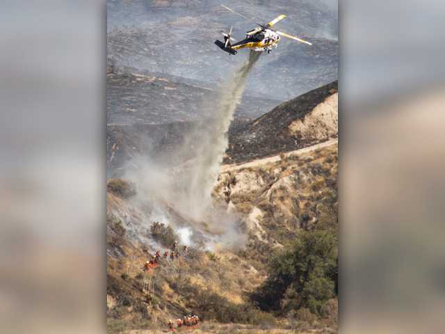 Helicopters drop water on the Sand Fire as fire crews work to contain it in Sand Canyon on Friday July 22, 2016. Signal photo by Jordan Glenn.