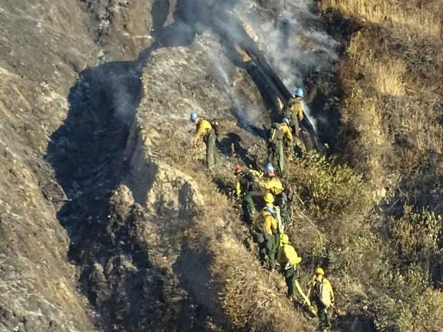Hand crews work on hot spots in steep terrain near Soledad canyon road where it passes under the 14 freeway. Signal photo by Dan Watson.
