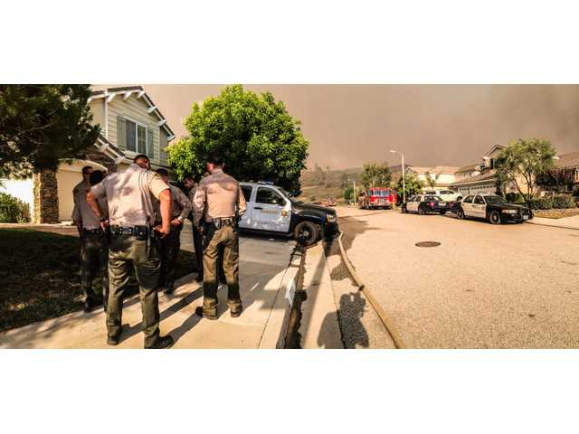 Sheriff's deputies prepare to evacuate residents on Heron Lane in Canyon Country. Signal Photo by Austin Dave