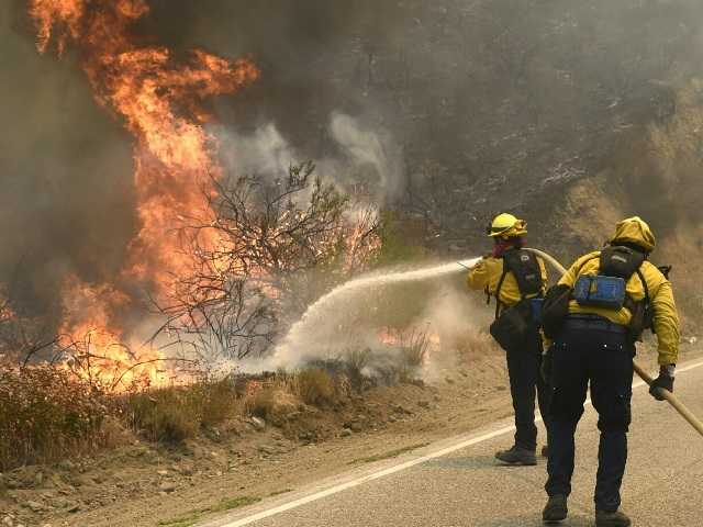 Firefighters douse a hot spot in Placerita Canyon on Monday. Signal photo by Dan Watson