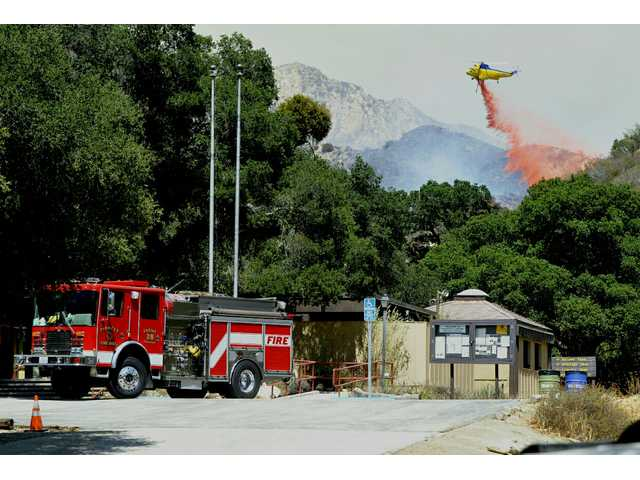 A helicopter drops fire retardant on an area about 3/4 of a mile east as seen from the Placerita Canyon Nature Center on Monday afternoon. Signal Photo by Dan Watson
