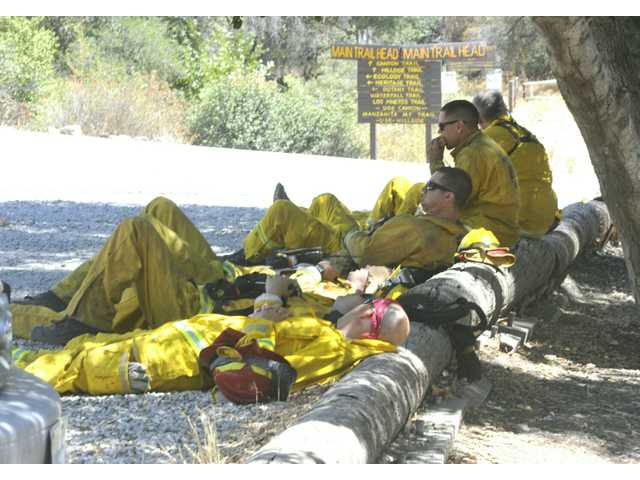 Firefighters from Pioneer, in Northern California, sit in the shade as they stand structure protection with three other engine companies at The Placerita Canyon Nature Center on Monday afternoon.