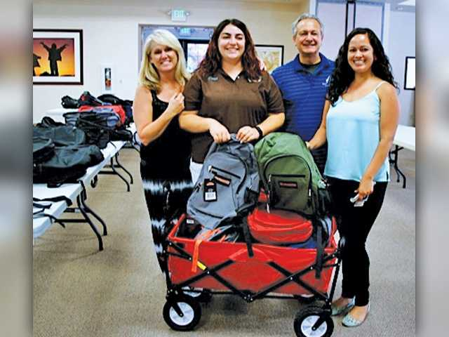 (l-r) Elks members Stacy McKenna, Teresa Handy, John Rivetti, and staff therapist Genesis Espinoza with some of the 270 backpacks collected and presented to the Child & Family Center on August 4. Courtesy photo