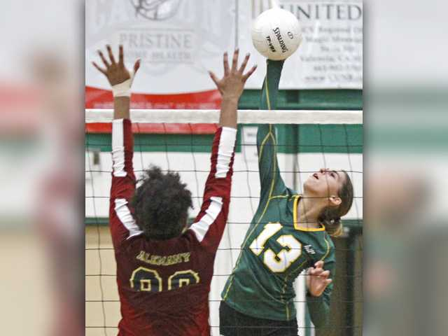 Canyon's Makela Lyons (13) hits the ball as Alemany's Renee Wheeler goes for the block Wednesday at Canyon High.